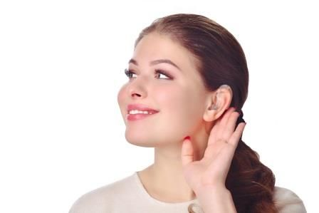 woman holding up her hand against her ear