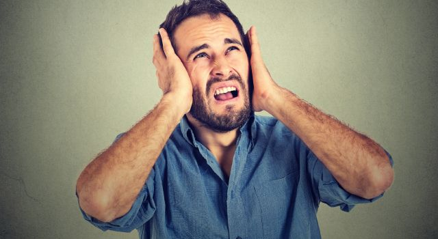 unhappy man blocking out noise with his hands