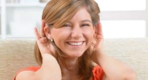 smiling woman holding her hands up to her ears