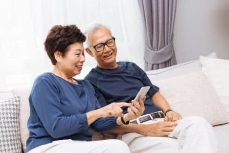 mature asian couple looking at a mobile phone