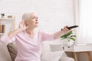 Senior woman cupping her hand behind ear to hear better
