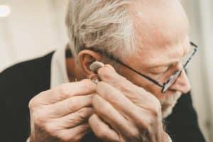 Older man putting his hearing aids on