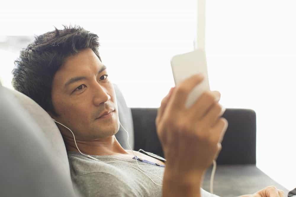 Man-listening-to-music-with-headphones-on-smart-phone-on-sofa